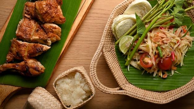 Salada de mamão comida tailandesa ou somtum com frango grelhado e arroz pegajoso vista de cima