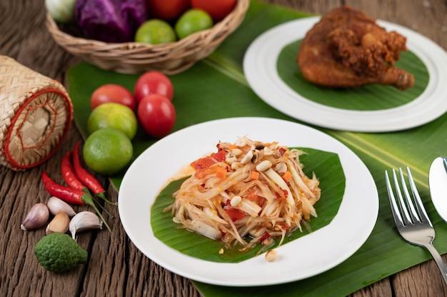 Salada de mamão tailandesa em um prato branco com folhas de bananeira com limão, tomate, berinjela, pimentão, alho, pimentão, salada e amendoim.