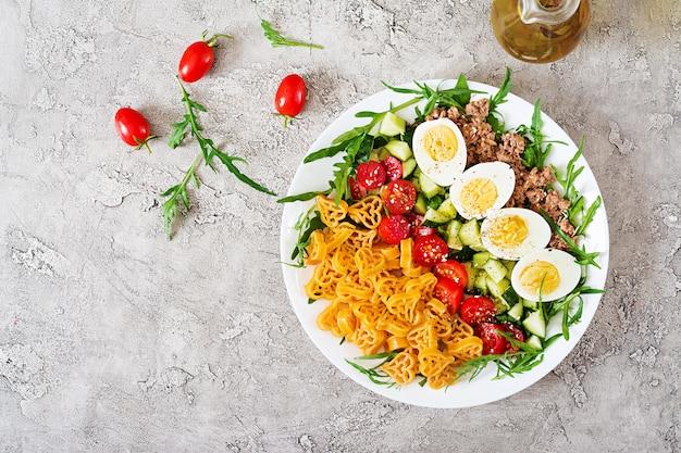 Salada de massa com legumes frescos, ovos e atum em uma bacia branca. comida de almoço.