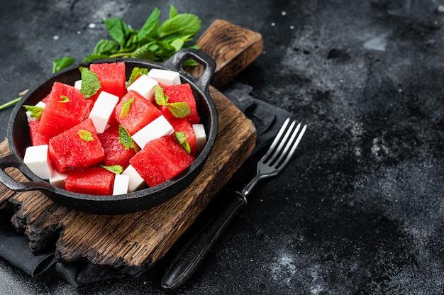 Salada de melancia orgânica saudável com queijo feta. fundo preto. vista do topo. copie o espaço.