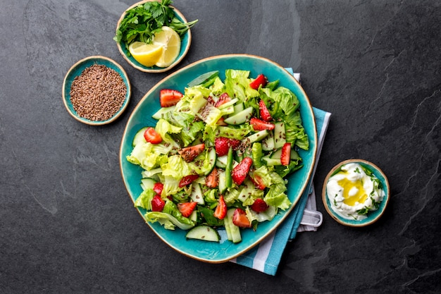 Salada de morango saudável alface com sementes de linho na vista superior da placa azul