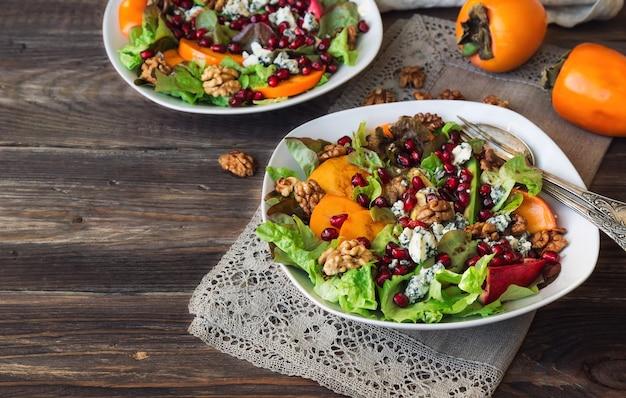 Salada de outono com caqui, romã, queijo azul e nozes em fundo de madeira rústica.