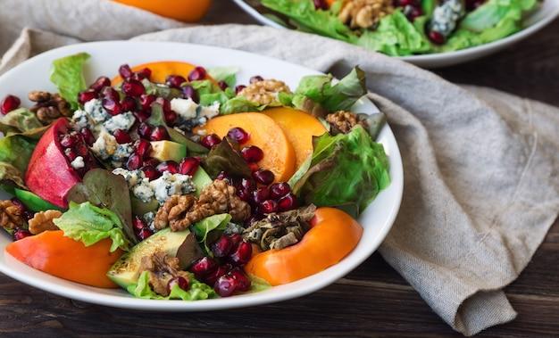 Salada de outono com caqui, romã, queijo azul e nozes na mesa de madeira rústica. foco seletivo.