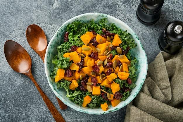 Salada de outono com couve, abóbora assada, sementes e cranberries secas em uma tigela. plano de fundo cinza. brincar. vista do topo.