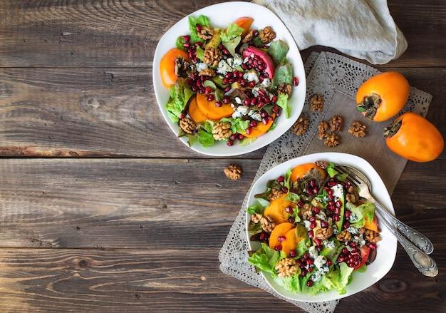Salada de outono com queijo azul de romã caqui e nozes em fundo de madeira rústico Foto Premium