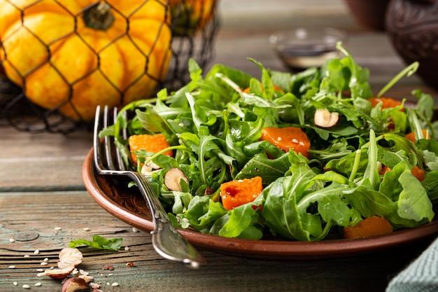 Salada de outono com rúcula assada de abóbora avelã e sementes de gergelim em prato marrom dieta paleo