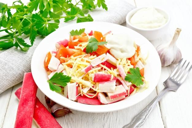 Salada de palitos de caranguejo, queijo, alho, tomate e maionese, pano de prato, salsa no fundo de uma tábua de madeira