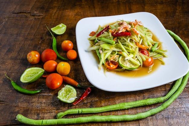 Salada de papaia comida tailandesa em uma mesa de madeira