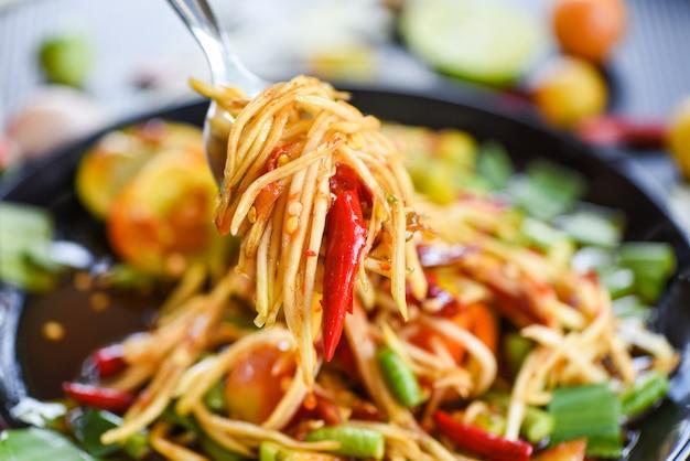Salada de papaia em uma forquilha feche acima do alimento tailandês picante da salada verde da papaia no foco seletivo da tabela, som tum tailandês