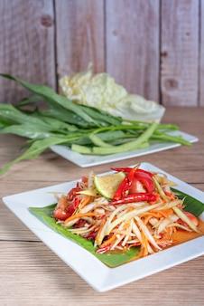 Salada de papaia picante em um prato com lado de legumes frescos