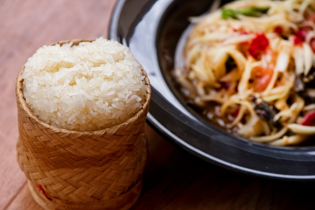 Salada de papaia tailandesa com arroz quente na madeira da tabela