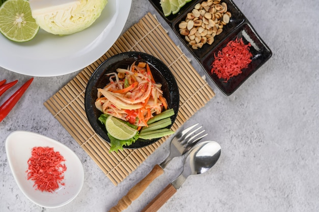 Salada de papaia tailandesa em um prato branco com arroz e camarão seco
