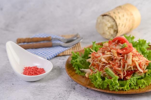 Salada de papaia tailandesa em um prato de madeira com arroz e camarão seco