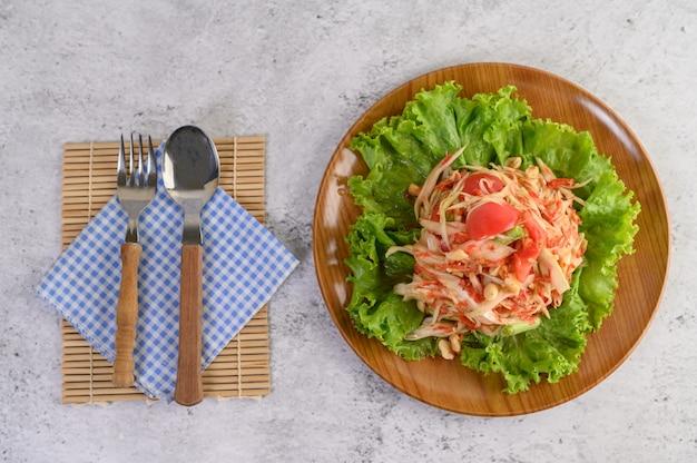 Salada de papaia tailandesa em uma placa de madeira com talheres