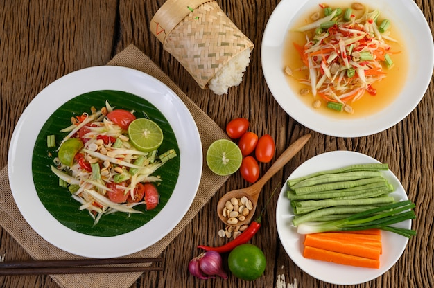 Salada de papaia (tum som) em um prato branco sobre uma mesa de madeira.