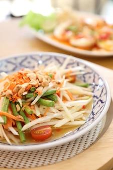 Salada de papaia verde ou som tam em comida de rua tailandês Foto Premium