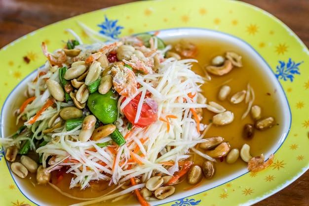 Salada de papaia verde picante estilo tailandês (som tum tailandês) na placa amarela
