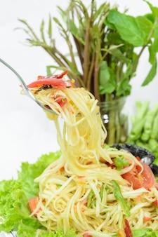 Salada de papaia verde picante ou somtum sobre fundo branco, comida tailandesa