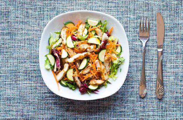 Salada de peito de frango com abobrinha e tomate cereja em um fundo de madeira