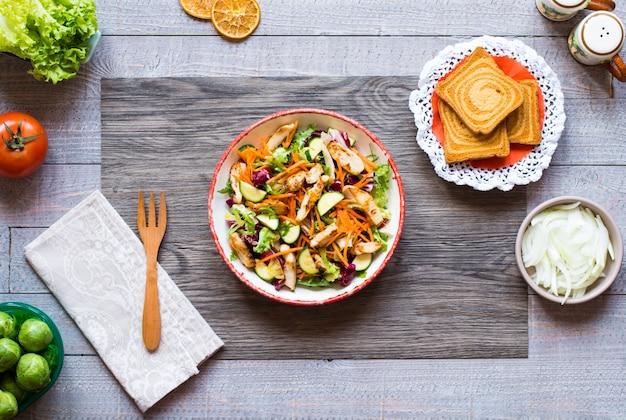 Salada de peito de frango com abobrinha e tomate cereja, em uma mesa de madeira