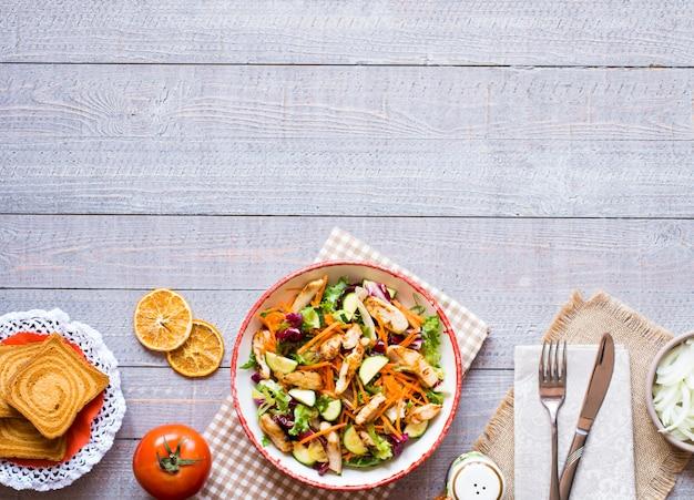Salada de peito de frango com abobrinha e tomate cereja, sobre um fundo de madeira