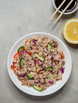 Salada de peixe com arroz em uma mesa de madeira branca. salada orgânica verde com fatias de atum em conserva. vista do topo.