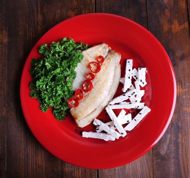 Salada de peixe fresco com legumes no prato em close-up de mesa de madeira