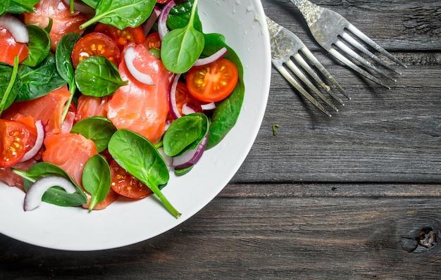 Salada de peixe. salada com rodelas de salmão, tomate e espinafre com suco de limão. sobre um fundo de madeira.