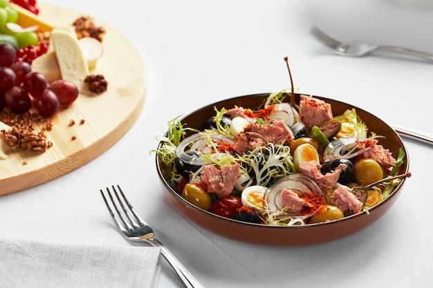 Salada de peixes em fundo claro, clássico niçoise com pedaços grandes de filé de atum, ovos, azeitonas e cebolas.