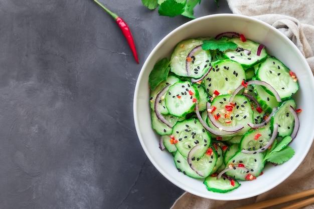 Salada de pepino asiática com cebola roxa, pimenta e gergelim preto em uma tigela branca sobre concreto cinza. vista do topo.