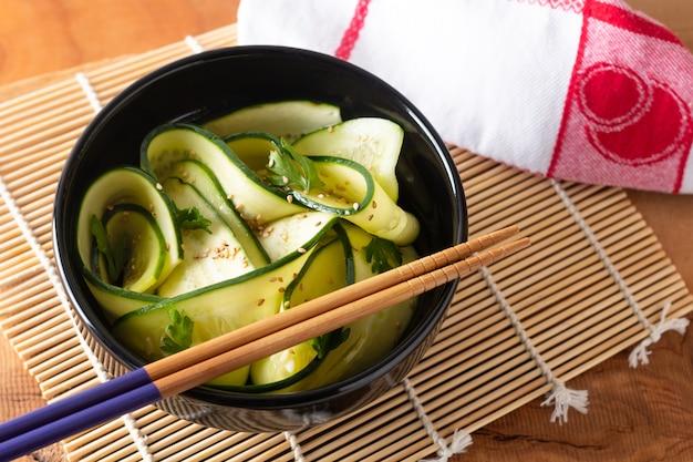 Salada de pepino de comida saudável com molho de soja e molho de gergelim na tigela preta