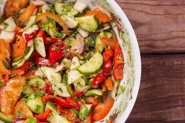 Salada de pepino e tomate com cebola na mesa de madeira
