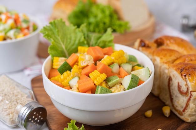 Salada de pepino, milho, cenoura e alface em um copo branco.