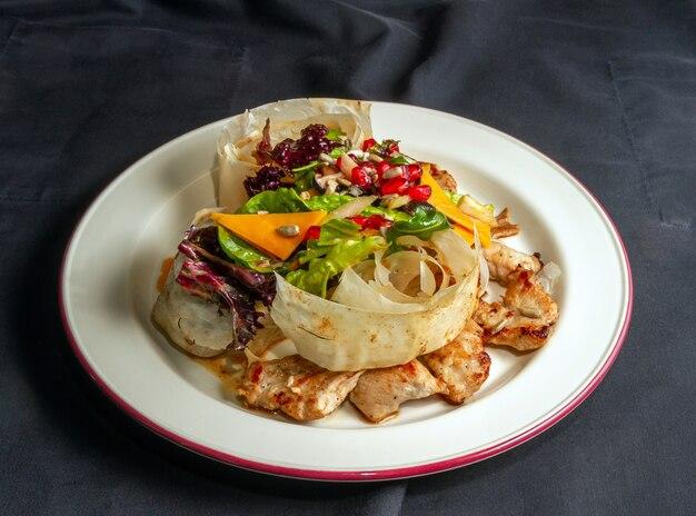 Salada de peru, guarnecida com pedaços de pão pita e sementes de romã