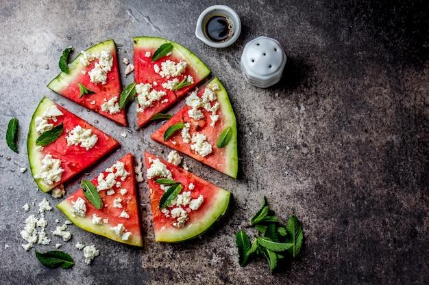 Salada de pizza fresca de melancia com queijo feta, hortelã, sal e óleo na pedra