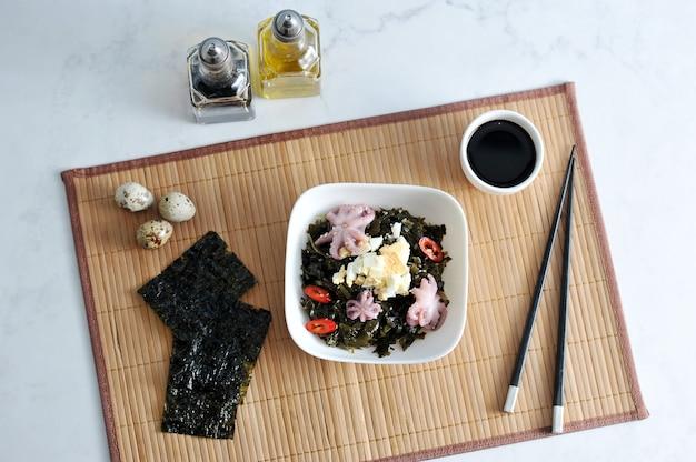 Salada de polvo de kaleuropa do mar, ovos e cebola em um guardanapo de bambu - vista superior