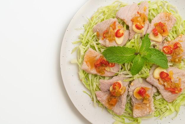 Salada de porco picante ou carne de porco cozida com limão, alho e molho de pimenta isolado no branco