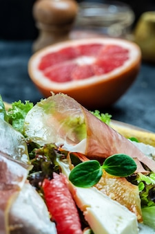 Salada de presunto crudo de presunto com queijo brie camembert e toranja, mistura para salada. comida saudável, plano de fundo de receita de comida. fechar-se.