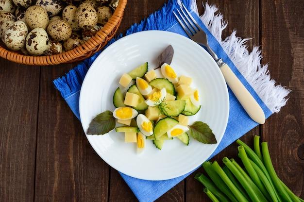 Salada de primavera italiana leve com pepino fresco, ovos de codorna, mussarela, azeite em um prato branco sobre um fundo de madeira. refeição dietética. a vista de cima
