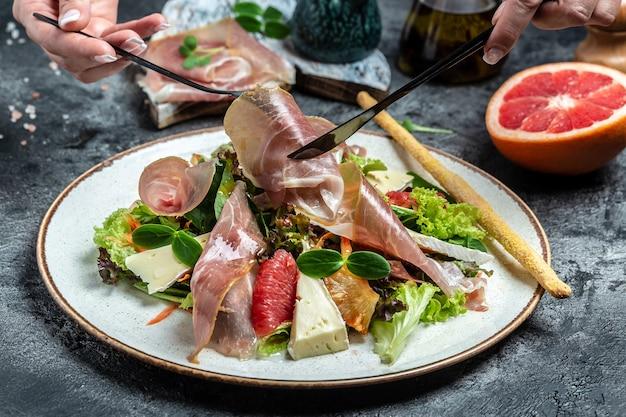 Salada de prosciutto di parma com toranja, mistura para salada, toranja, tomate cereja, queijo parmesão. lanches frios. menu de restaurante, dieta, receita de livro de receitas,