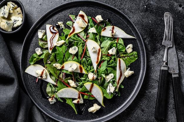 Salada de queijo azul com peras, nozes, acelga e rúcula. fundo preto. vista do topo.