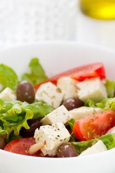 Salada de queijo com legumes em uma tigela branca em fundo branco