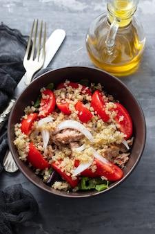 Salada de quinua com atum, tomate e alface em uma tigela marrom