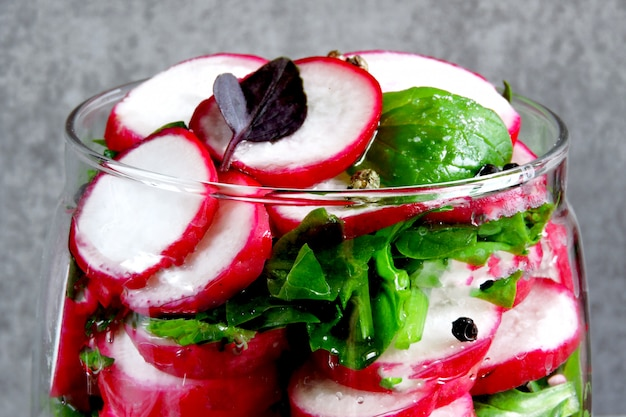 Salada de rabanete com espinafre em uma jarra. salada de fitness na jarra. salada de legumes em uma jarra para ir.