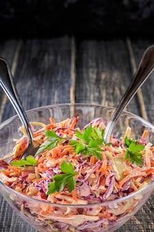 Salada de repolho caseiro na bacia em de madeira escuro.