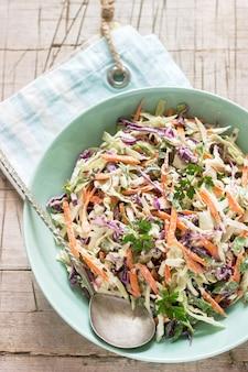 Salada de repolho de couve, cenoura e várias ervas com maionese em um prato grande, sobre um fundo de madeira.