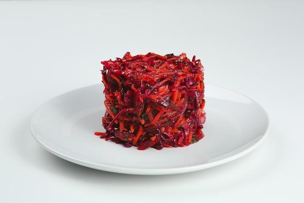 Salada de repolho de legumes frescos, beterraba, cenoura. salada de beterraba com repolho em prato branco isolado