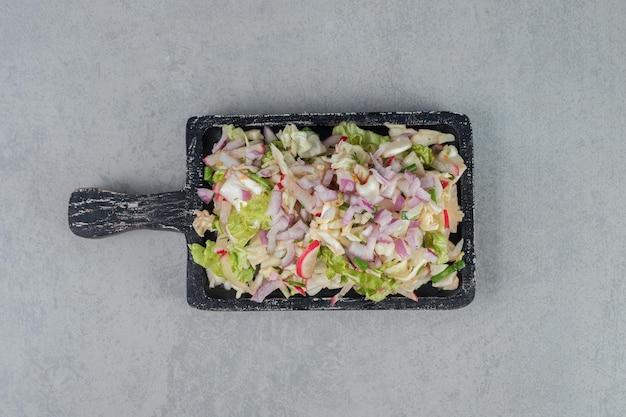 Salada de repolho e alface em uma placa de madeira.
