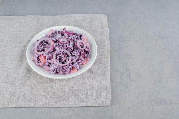 Salada de repolho e cebola roxa em um prato de cerâmica branca.