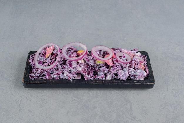 Salada de repolho e cebola roxa em uma travessa.